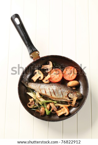 Pan fried trout with button mushrooms and tomatoes - stock photo