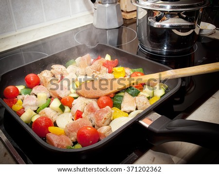 Pan full of various vegetables and meat captured during cooking some delicious meal. - stock photo