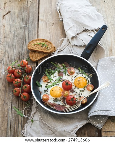 Pan of fried eggs, bacon and cherry-tomatoes with bread on rustic wood table surface. Top view - stock photo