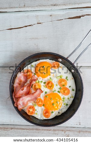 Pan of fried eggs, bacon and tomato. Top view. - stock photo