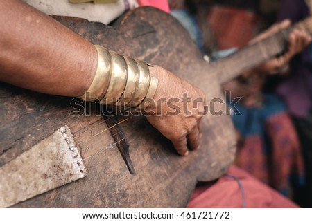 Pan Pet, Myanmar - May 25, 2016: Padaung (Karen) woman playing traditional guitar near the house, Myanmar