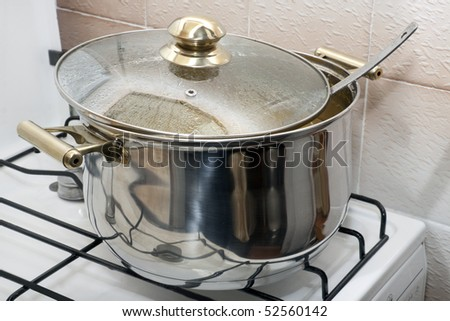 pan with golden handles for cooking on a gas-stove - stock photo
