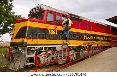 PANAMA CITY, PANAMA - AUGUST 12, 2009: Man enters cab of train, Panama Canal Railroad. - stock photo