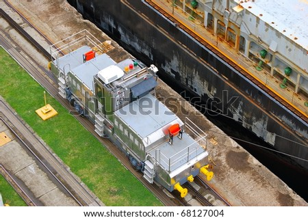 PANAMA - OCTOBER 6. In July 2009, the Panama Canal Authority awarded contracts to a consortium of companies to build six new locks by 2015. Locomotive towing a ship at Balboa. October 6, 2010, Panama - stock photo
