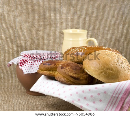 panary rolls lie on a napkin in a basket on a background a pot from clay and jug - stock photo
