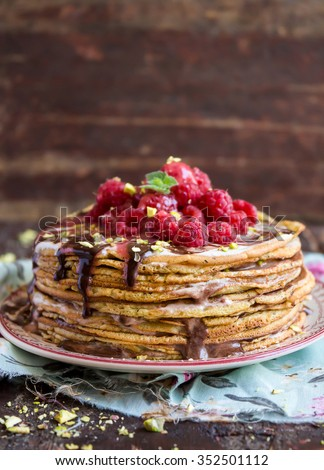Pancake cake with chocolate sauce, raspberry, pistachios nuts and mint on a dessert plate, selective focus - stock photo