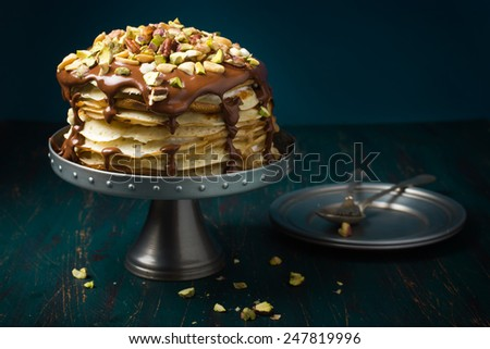 pancake cake with custard cream and chocolate topping and nuts - stock photo