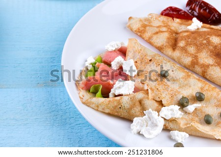 Pancake day, mardi gras, maslenitsa background. Thin rolled pancakes, crepes with salmon, feta cheese and dried tomatoes. Traditional Russian dish. - stock photo