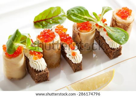 Pancake Roll with Cream and Salmon Caviar. Garnished with Lemon Slice - stock photo