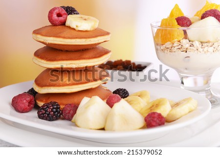 Pancake with fruits on plate and muesli on table on bright background