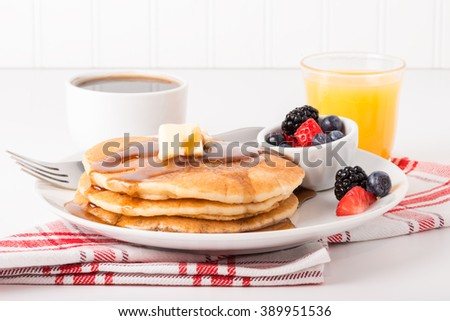 Pancakes and maple syrup with coffee and orange juice. - stock photo