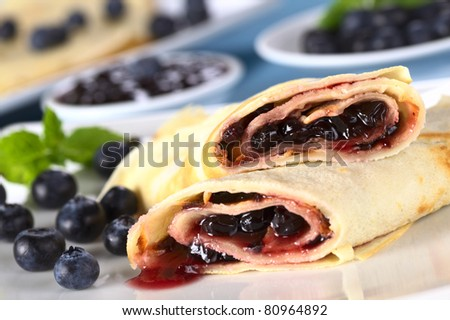 Pancakes filled with blueberry jam with fresh blueberries on the plate and jam in the back (Selective Focus, Focus on the front of the upper pancake roll) - stock photo