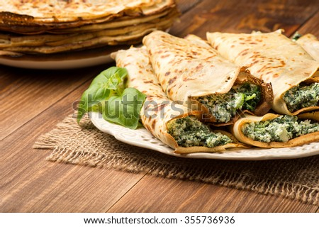 Pancakes filled  with spinach and cheese  on the wooden surface. - stock photo