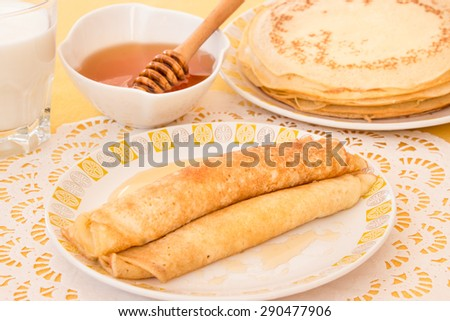 Pancakes rolled in a tube and poured honey on a plate, a glass of milk, a bowl of honey, a plate with a stack of pancakes. Pancakes and honey. Horizontal shot. Close-up.  - stock photo
