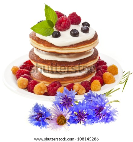Pancakes stack with fresh berries and flowers on white background - stock photo
