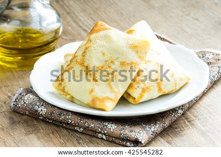 Pancakes, thin crepes stuffed with peas and bacon, to Russian Maslennitsa - stock photo
