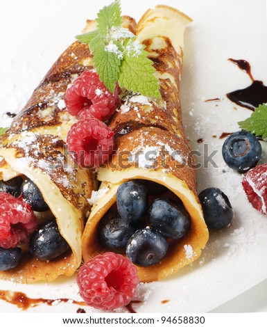 pancakes topped with blueberries,raspberries, mint and Powdered sugar - stock photo