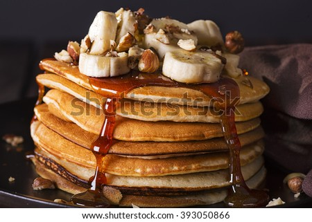 pancakes with banana and hazelnuts on dark background - stock photo