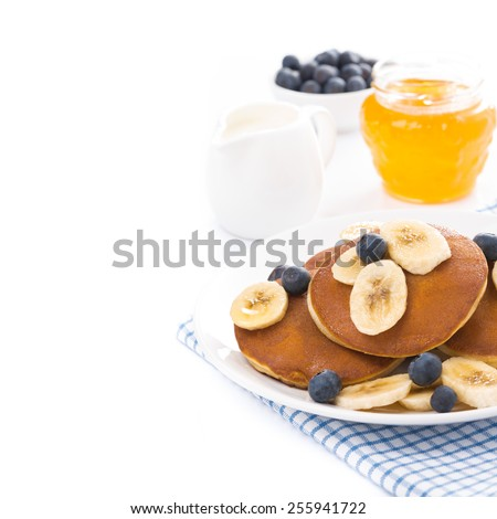 pancakes with banana, honey, blueberries and yogurt, isolated on white - stock photo