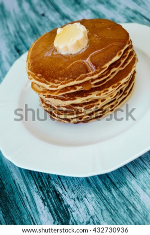 Pancakes with butter and honey on white plate on blue wooden background. Stack of wheat golden pancakes or pancake cake, closeup. - stock photo