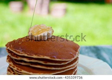 Pancakes with butter and honey on white plate on  in garden or on nature background. Maple syrup pouring on pancakes stack.  - stock photo