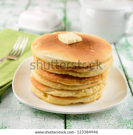 Pancakes with butter on a white table