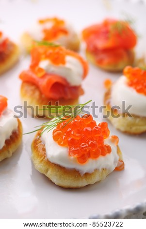 pancakes with caviar and salmon on white plate - stock photo