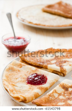 Pancakes with cranberry jam. Stack of pancakes and jam in background - stock photo