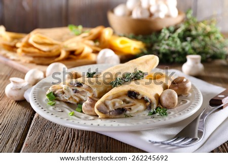 Pancakes with creamy mushrooms in plate on wooden background - stock photo