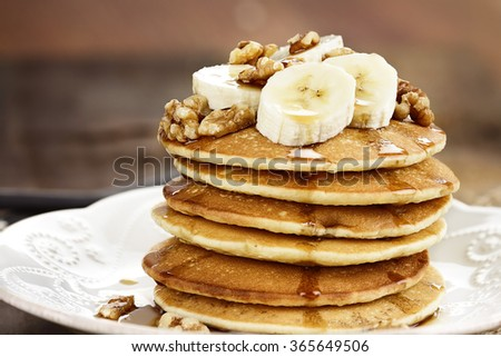 Pancakes with fresh bananas and walnuts with extreme shallow depth of field. - stock photo