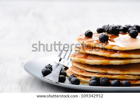Pancakes with fresh blueberries and maple syrup, plenty of copy space - stock photo