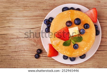 Pancakes with fresh blueberry and strawberry on wooden background - stock photo