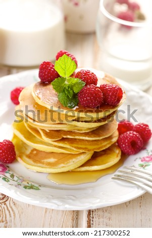 Pancakes with fresh raspberries and maple syrup - stock photo