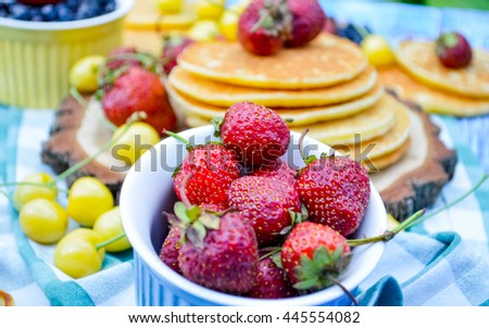 Pancakes with fresh raspberries, strawberries, cherries, blueberries on blue wooden background in garden or on nature - stock photo