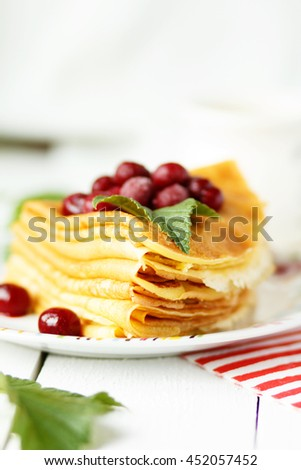 Pancakes with frozen cherries on the table. Breakfast.