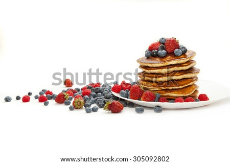 Pancakes with honey and berries on white background