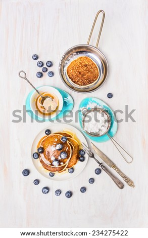 Pancakes with honey and blueberries on white wooden background, top view - stock photo