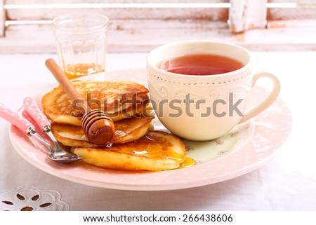 Pancakes with honey and cup of tea - stock photo