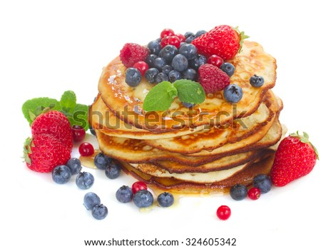 Pancakes with honey and  fresh berries isolated on white background