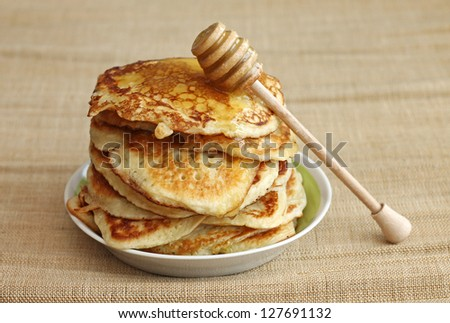 pancakes with honey and wooden dipper on canvas background, close-up - stock photo