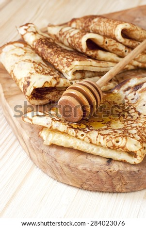 Pancakes with honey on wooden board - stock photo