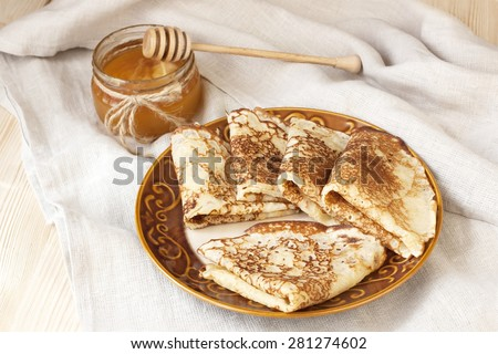 Pancakes with honey syrup on ceramic plate. Traditional crepes for pancake week or Shrovetide - stock photo