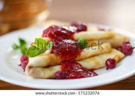 pancakes with jam and berries on a plate - stock photo