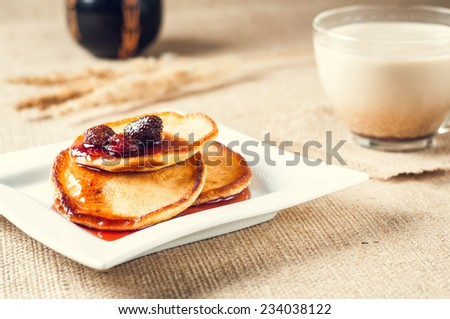 pancakes with jam and coffee on burlap background - stock photo