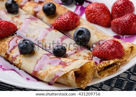 pancakes with jam, syrup and fruits on white plate - stock photo