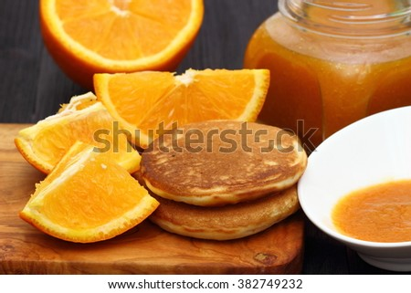 pancakes with oranges and orange jam in glass jar - stock photo