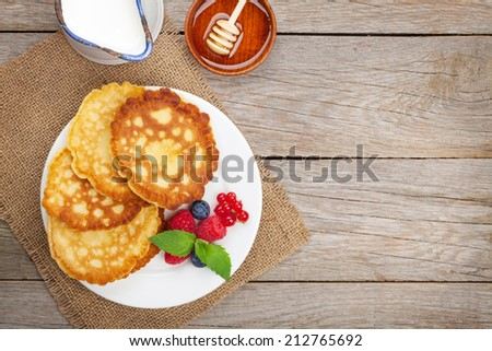 Pancakes with raspberry, blueberry, milk and honey syrup. On wooden table with copy space - stock photo