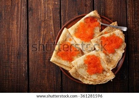 Pancakes with red caviar at home. Salty snack for Shrovetide. - stock photo