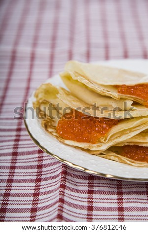 Pancakes with red caviar on a table. Shrovetide.