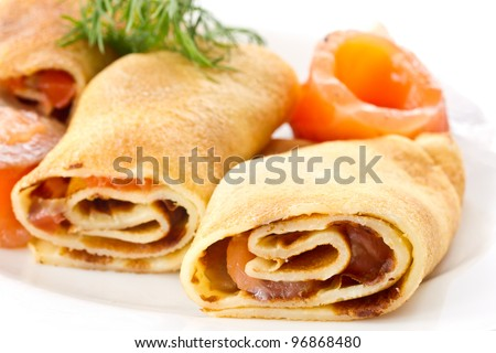 Pancakes with salted red fish on a white plate - stock photo